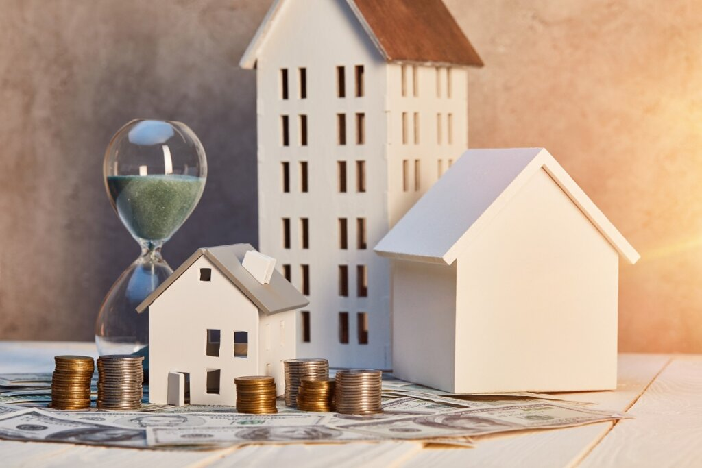 houses models, coins and cash, hourglass on white wooden table with sunlight, real estate concept
