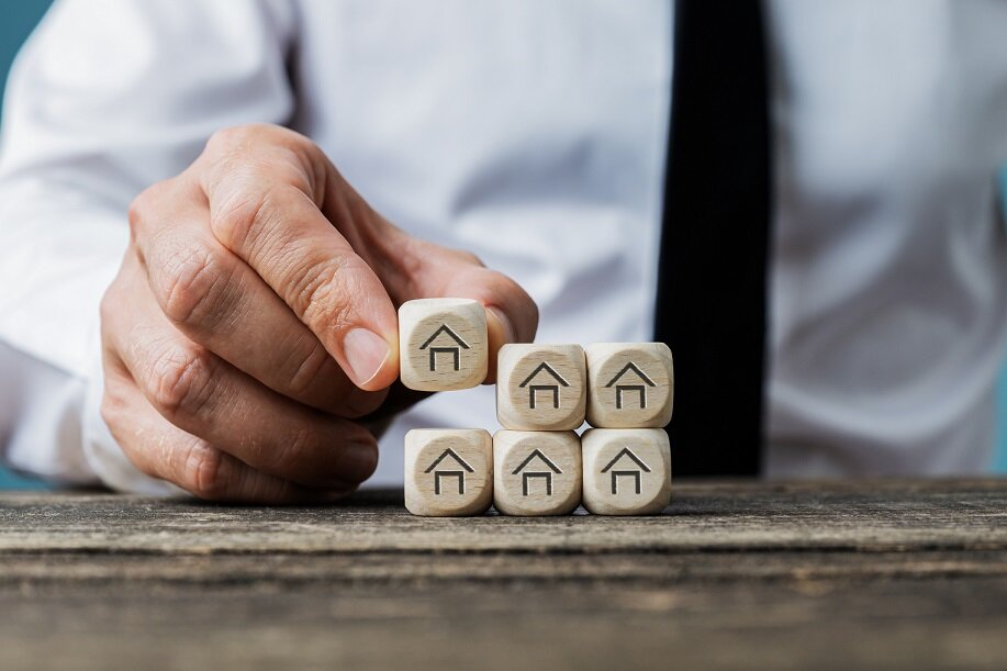 Front view of real estate agent stacking wooden dices with house symbols on them in a conceptual image.