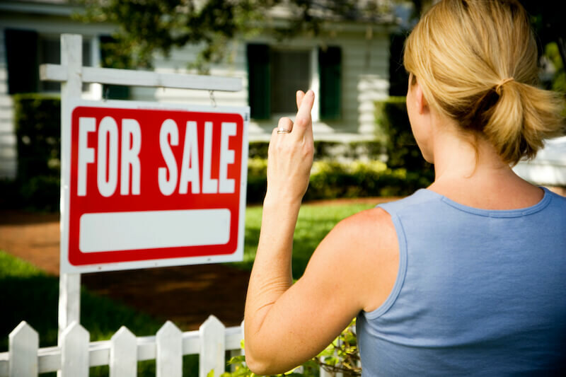 Woman standing by a for sale sign outside a family house, fingers crossed, hoping to sell house as is