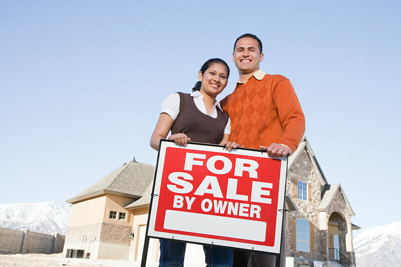 Couple holding For sale by owner sign wants to sell house fast