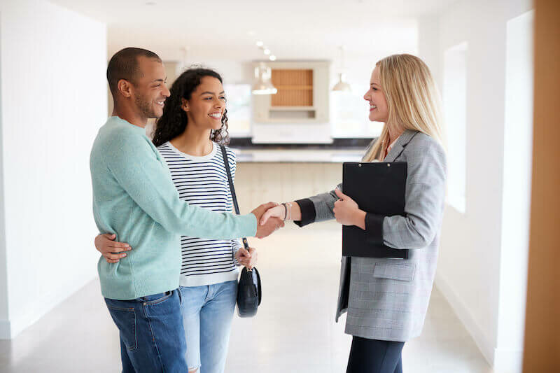 couple selling house welcoming a buyer