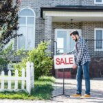 man putting a sale sign - house for sale fast