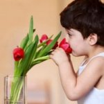 kid smelling flowers