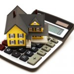 House sitting on calculator isolated on white background