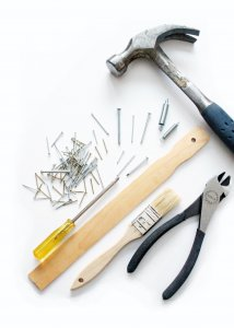 Assortment of tools for building hammer, pliers, nails, and screwdriver