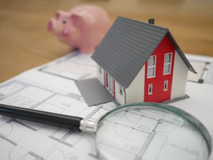 Magnifying glass with small home and house plans along with piggy bank
