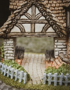 miniature model of a tiny home with white picket fence
