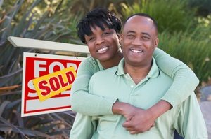 Happy African American Couple in Front of Sold Home For Sale Real Estate Sign.