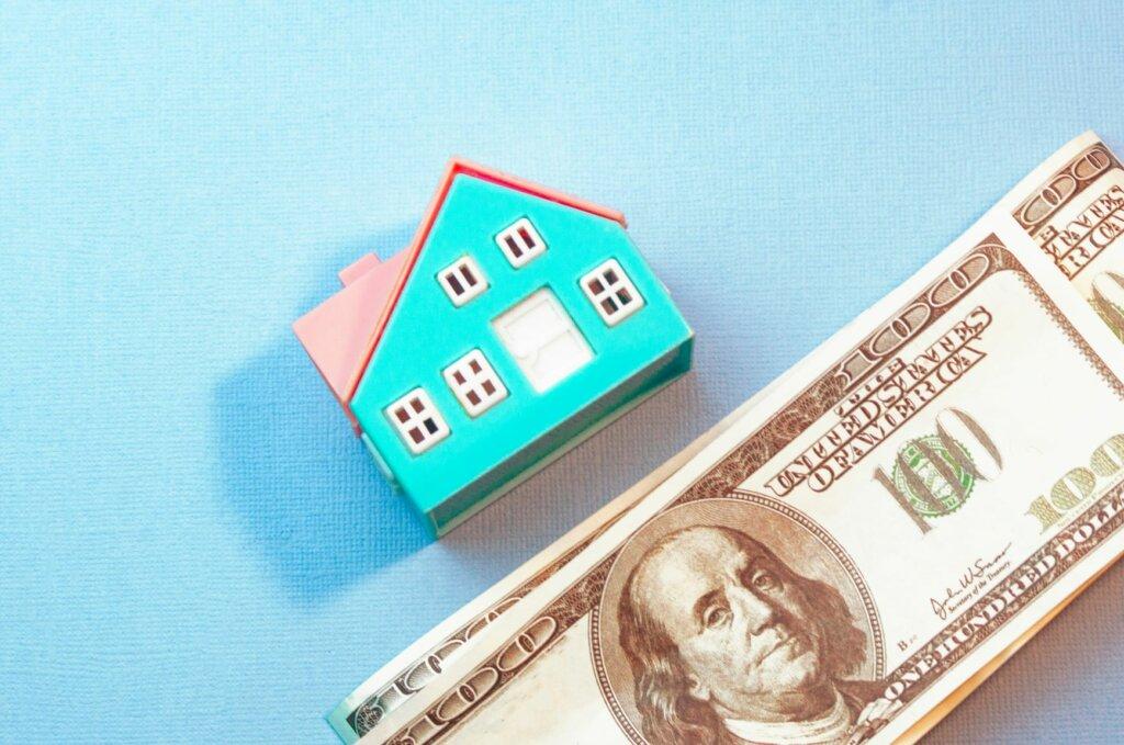 model house with hundred dollar bills