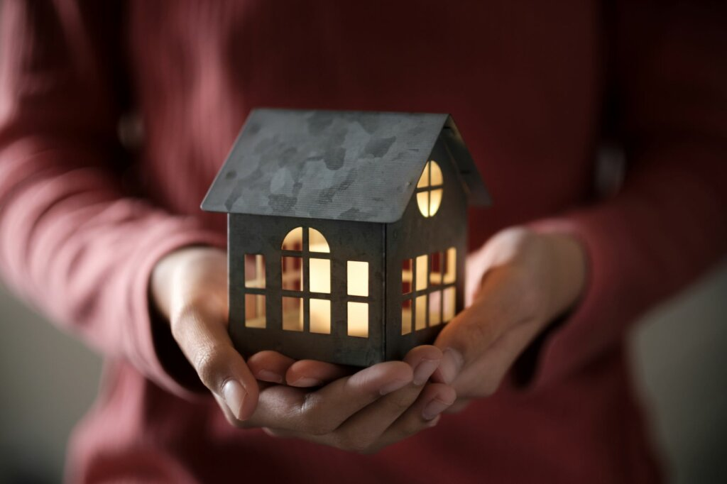 hands holding a toy model house