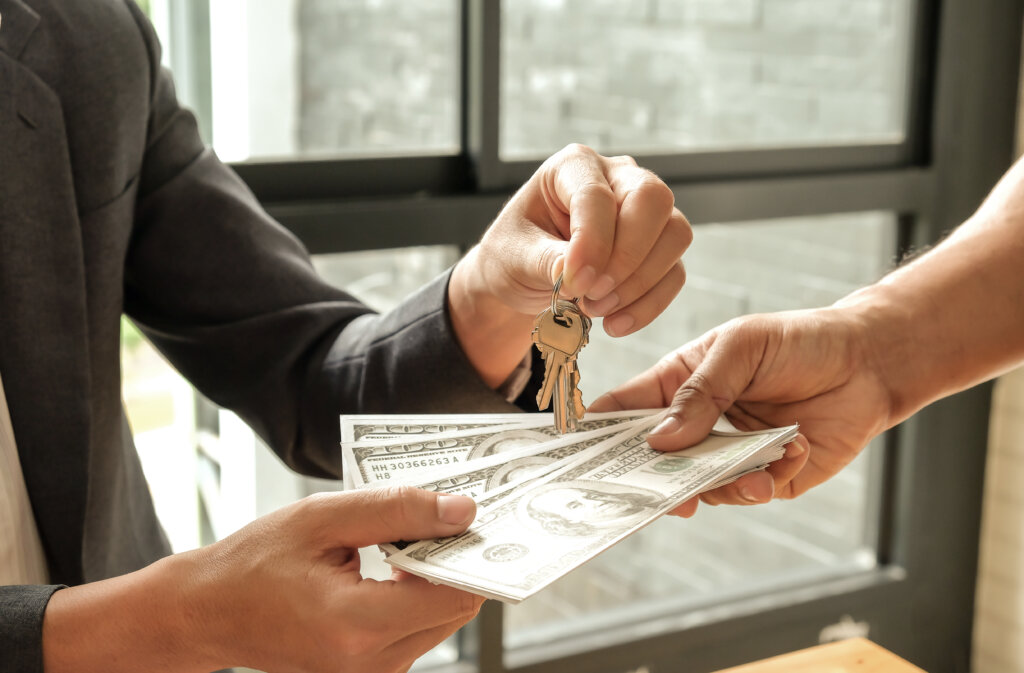 buyer and seller exchanging money and house keys