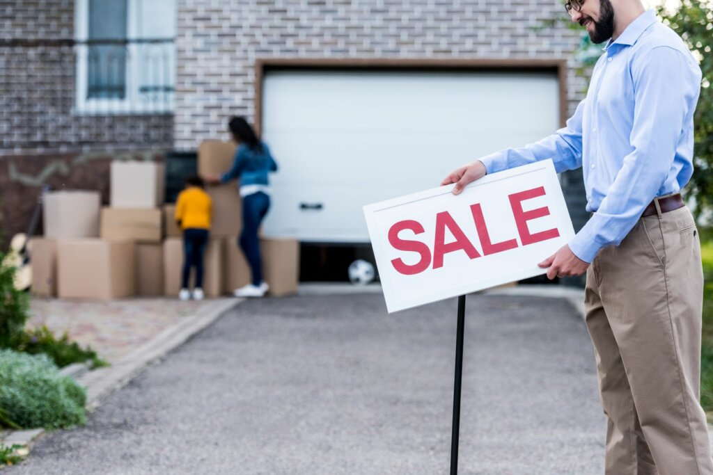 man holding a sale sign - house for sale as-is in Kansas City