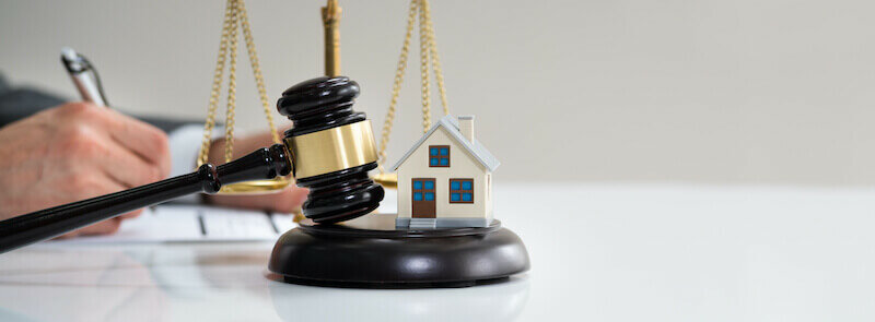 hand with gavel and model house - Minneapolis House Selling Laws