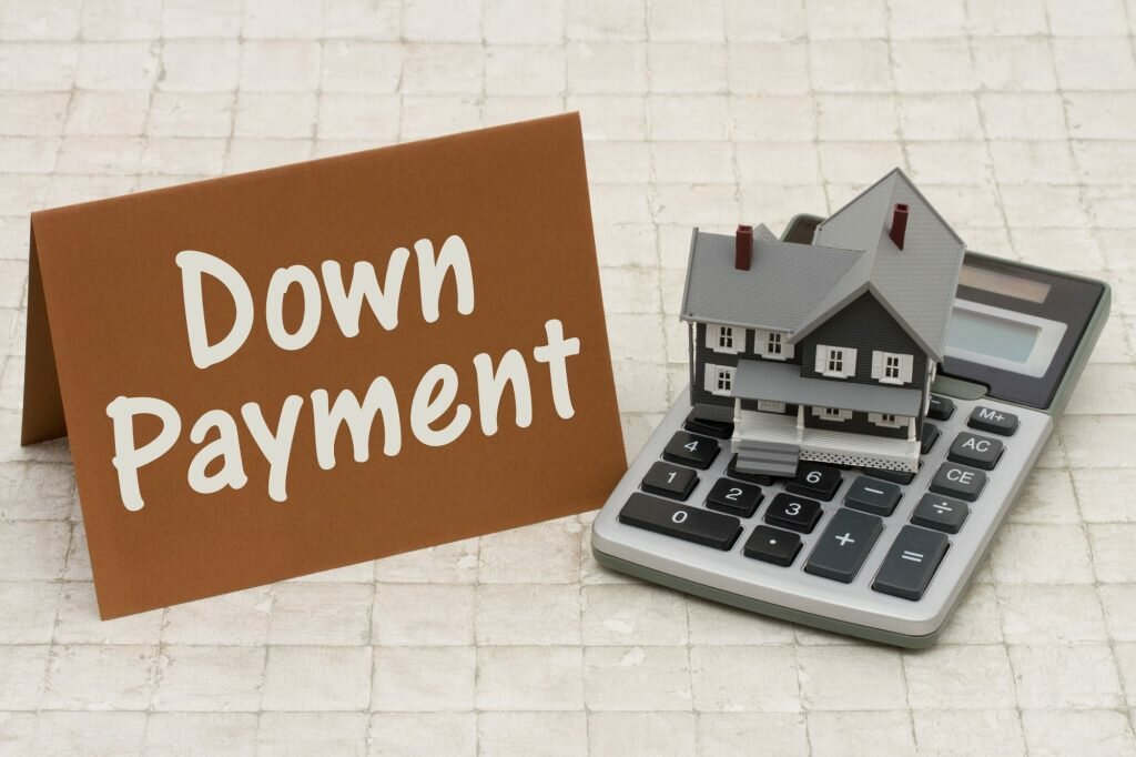 Picture of house, calculator and money to represent property down payment by a credible home buying company in greenville nc