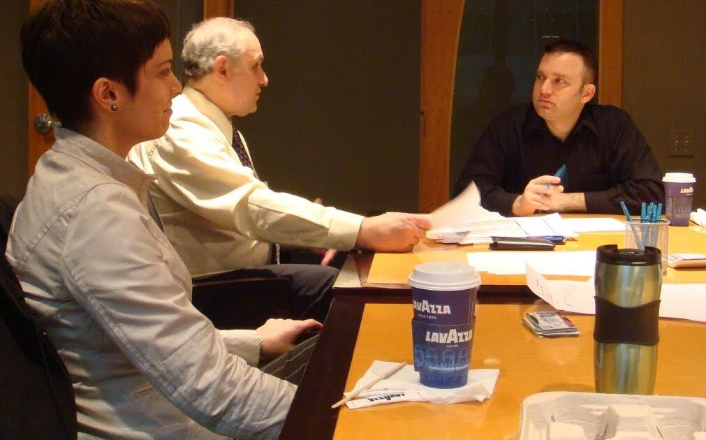 Three people at closing table with a credible home buying company in greenville nc