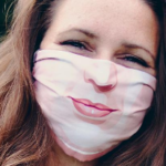 woman smiling with mask on who is moving during coronavirus