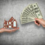 someone handing cash to another person for a house when they refinance or sell their house in greenville nc