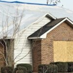 House with windows boarded and roof tarped that needs to be sold in Greenville NC