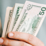 Hand holding cash saved while selling your house in Greenville NC