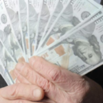 Hands holding money as you consider a cash offer for your home in greenville nc
