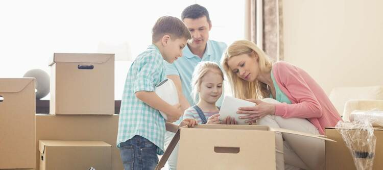 family packing a box while they prepare for moving in greenville nc