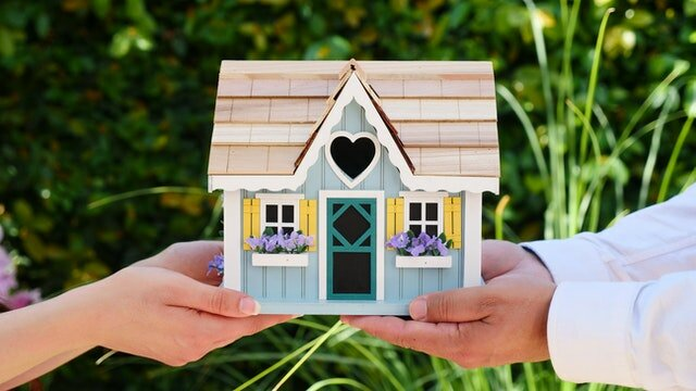 Two people holding a wooden toy house