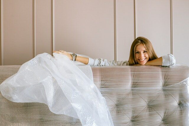 A woman unpacking her bed in her new home