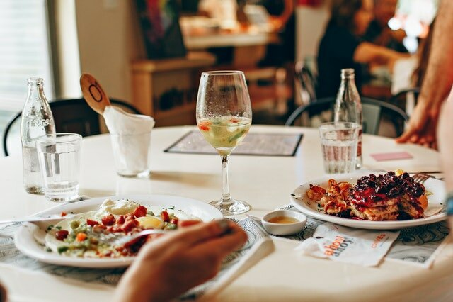 A restaurant table with two different dishes and a glass of wine.