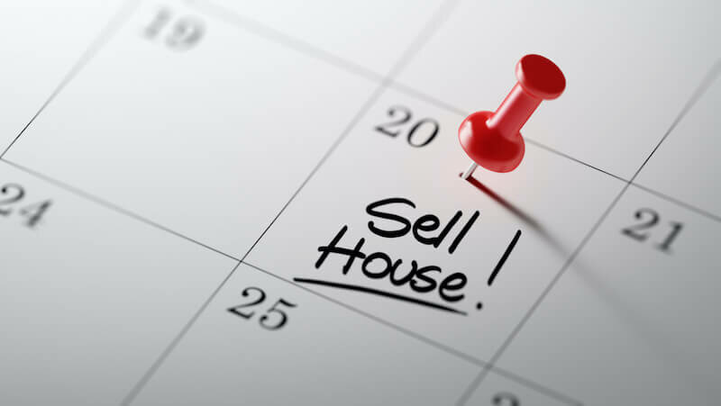 The words Sell House written on a calendar with a red push pin