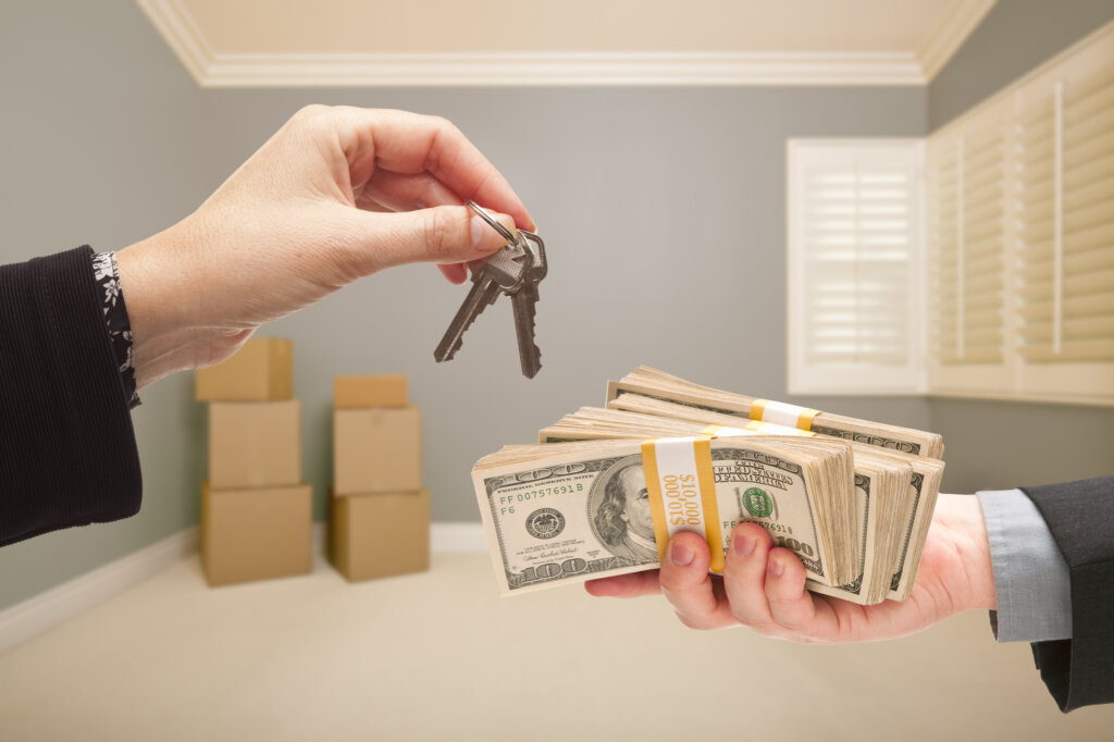 one hand exchanging keys and the other exchanging cash
