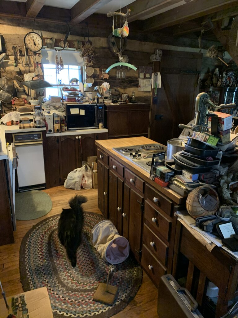 outdated kitchen with lots of clutter all in it and a cat on the ground