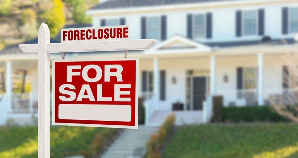 """house with a """"for sale"""" sign that says foreclosure on top to signify the foreclosure process"""