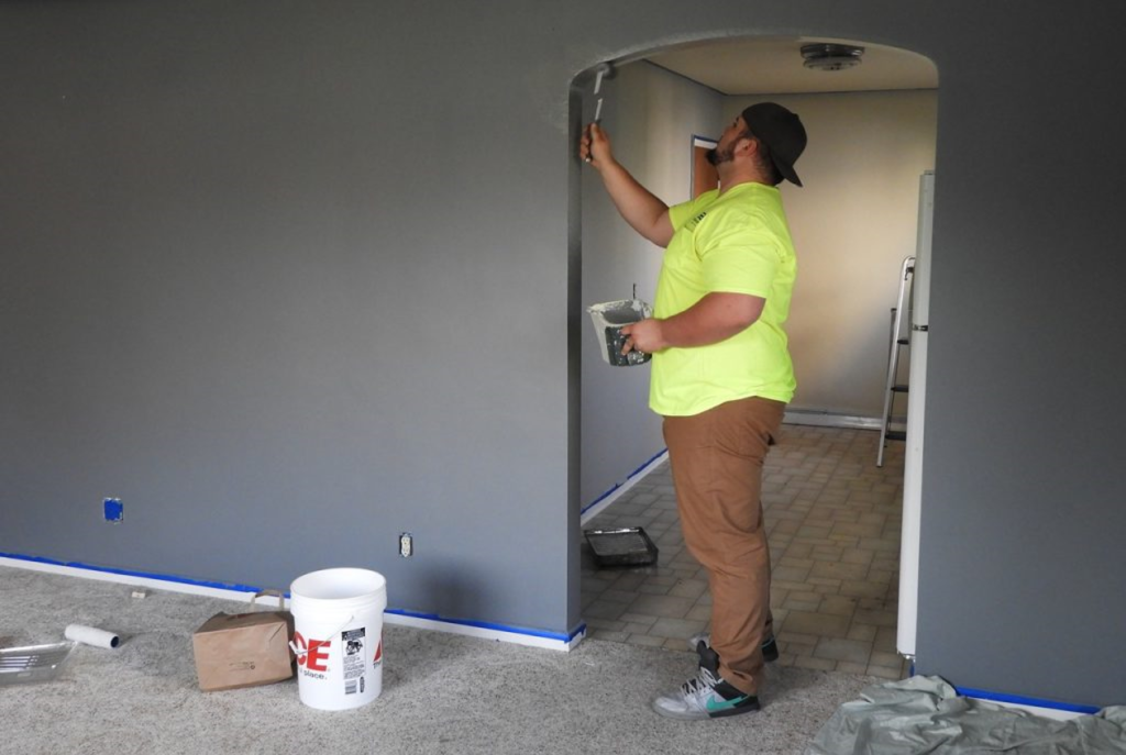white male with green shirt and tan pants painting a doorway gray