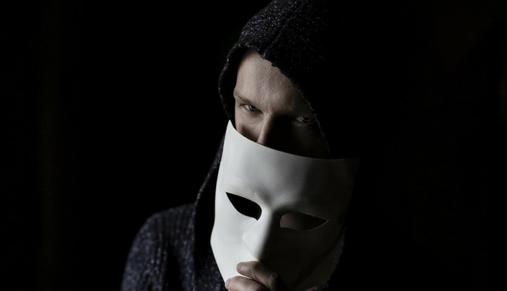 white man in black hoody holding a white mask over his face to signal deception