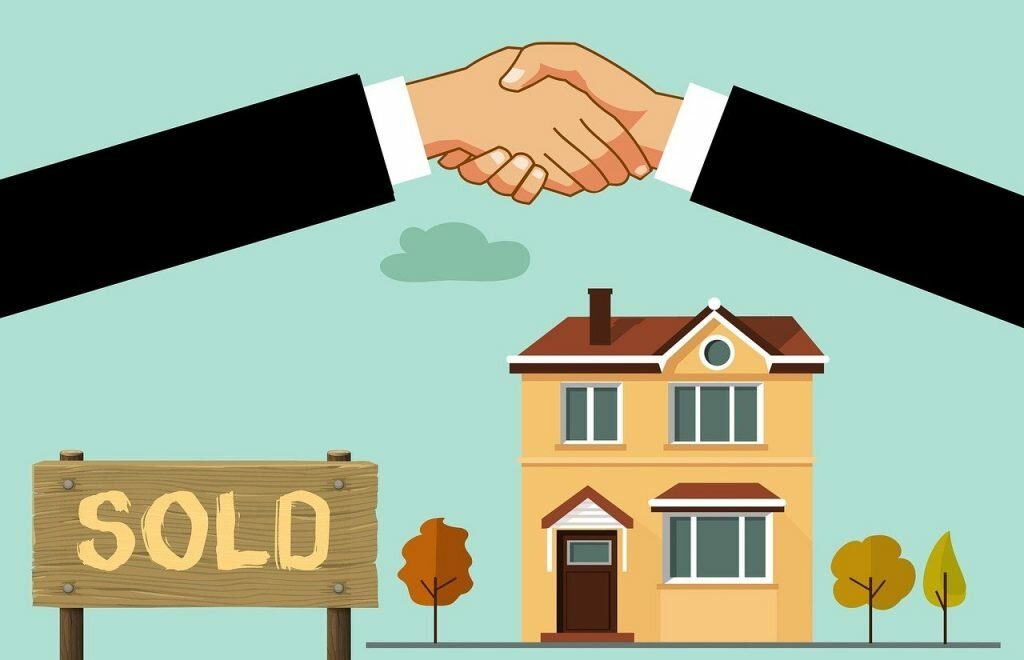 """2 cartoon hands shaking hands with a house and """"sold"""" sign below it"""