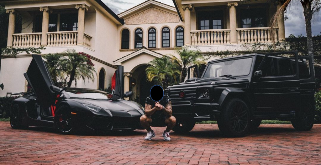 real estate wholesaler posing in front of nice cars and large house