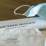 Defaulting renter with facemask receives letter giving notice of eviction
