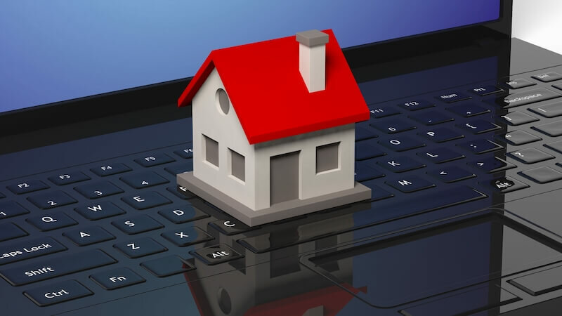 Model house and black laptop - sell my house online Florida
