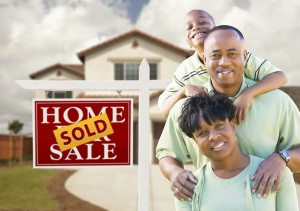 Happy African American Family in Front of New House and Sold Rea