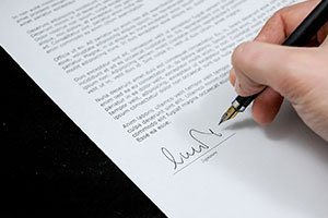 hand with pen signing a contract with We Buy Houses Nashville company