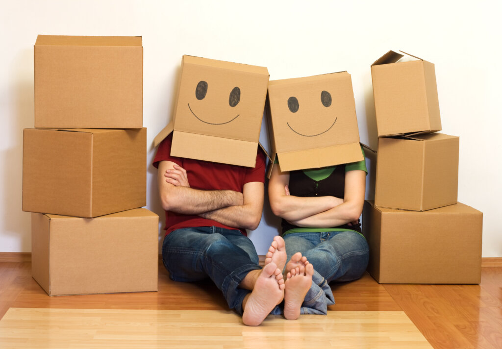 Couple sitting beside boxes.