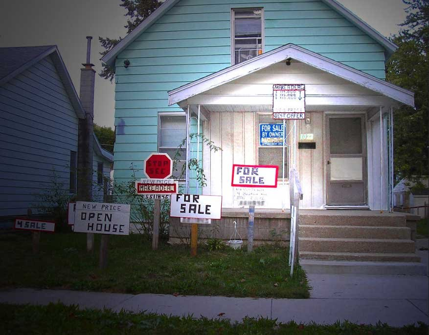 A house being sold by its owner with an absurd number of handmade for sale signs.