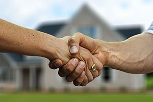 Hand Shake with house background