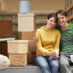 smiling young couple sitting back of moving van