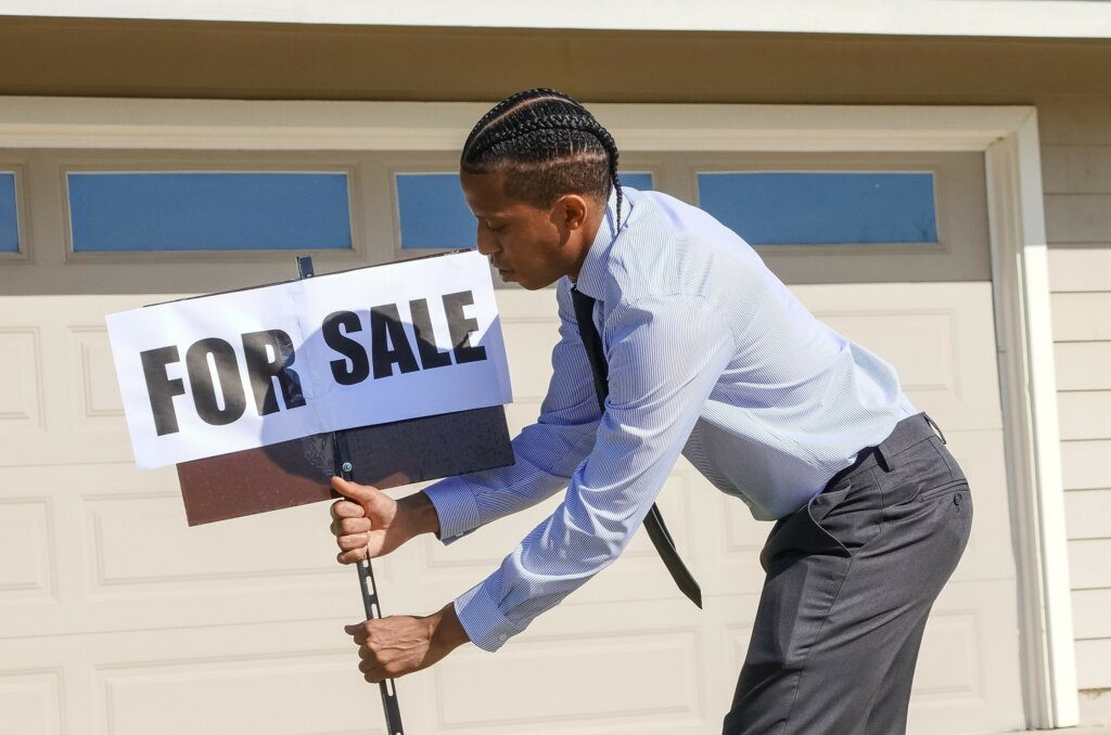 real estate agent placing a for sale sign