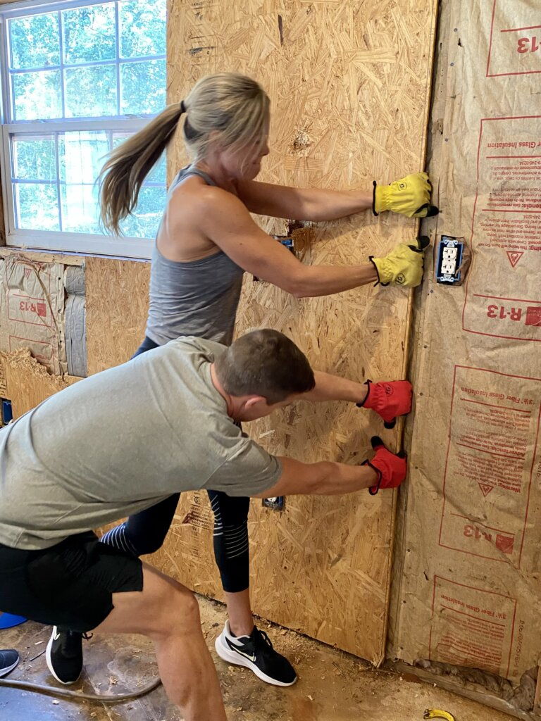 Man and Woman pulling plywood off a wall