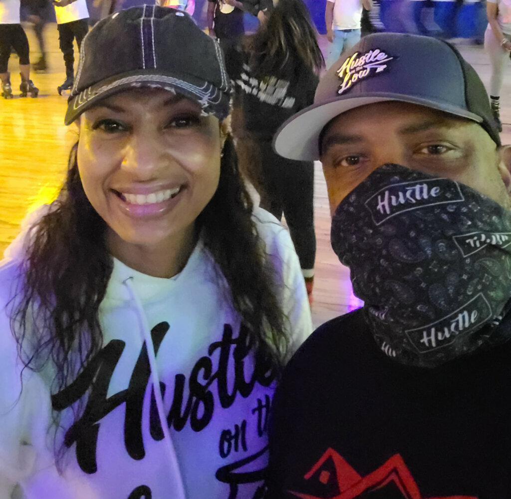 Houstle Solutions Inc Owner and President smiling together wearing a Hustle On the Low hoodie and hat