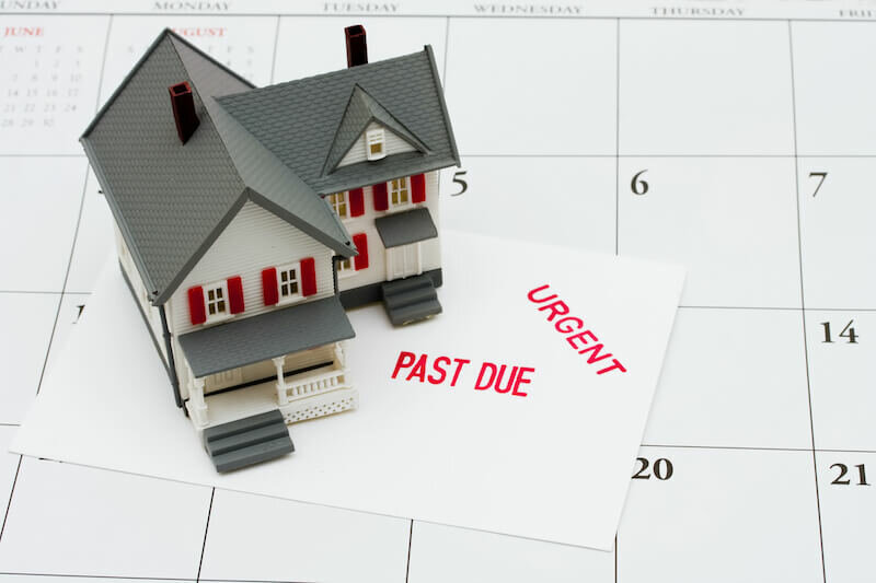 An overdue bill beside a house on calendar background, overdue mortgage