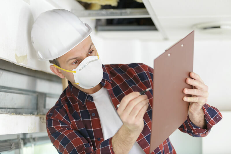 man inspecting a damaged house wearing a dust mask