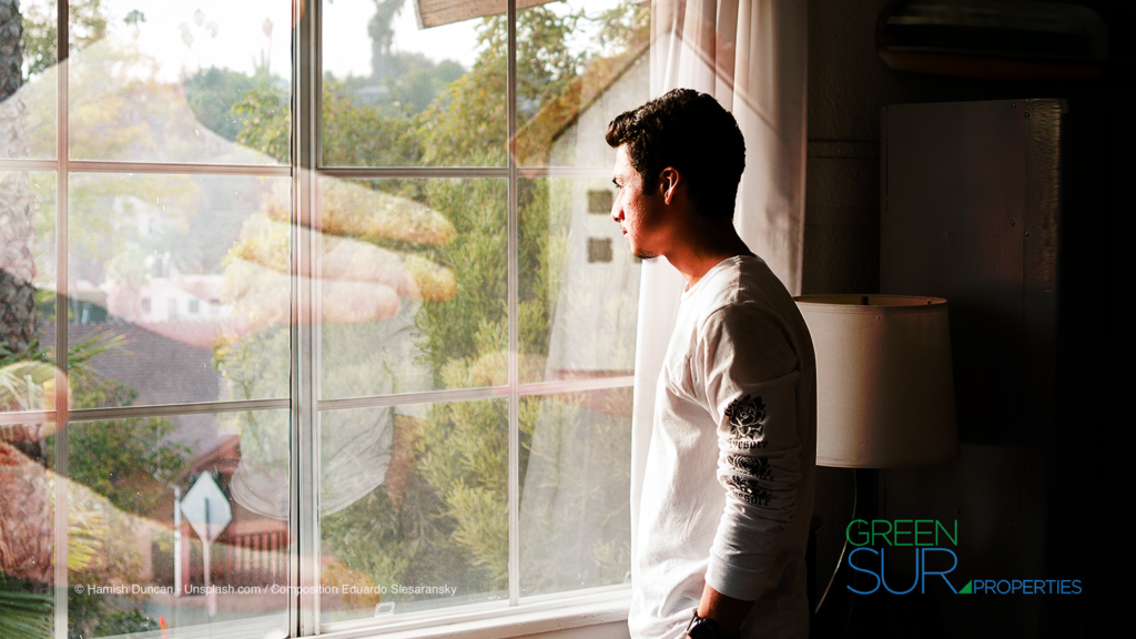Young man looking over window. Reflection big hands gifting house.